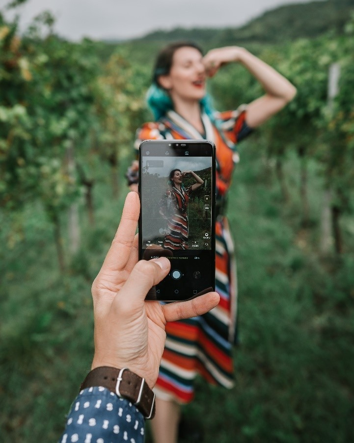 A man holding up an LG smartphone to take a photo of a woman posing as she eats grapes.