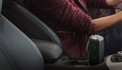 LG PuriCare Mini standing in the cup holder between driver and front passenger seat