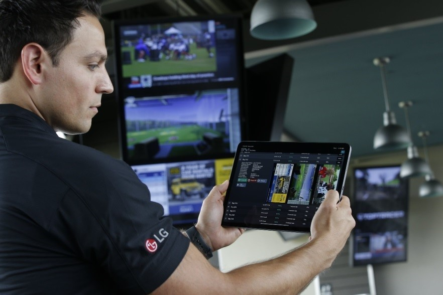Another image in which a man holds up a SAVI Canvas tablet to remotely manage the information displayed on LG's commercial digital signage solutions.