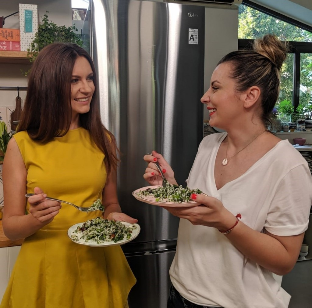 Two women enjoy the healthy fresh meals they prepared earlier in front of an LG refrigerator.