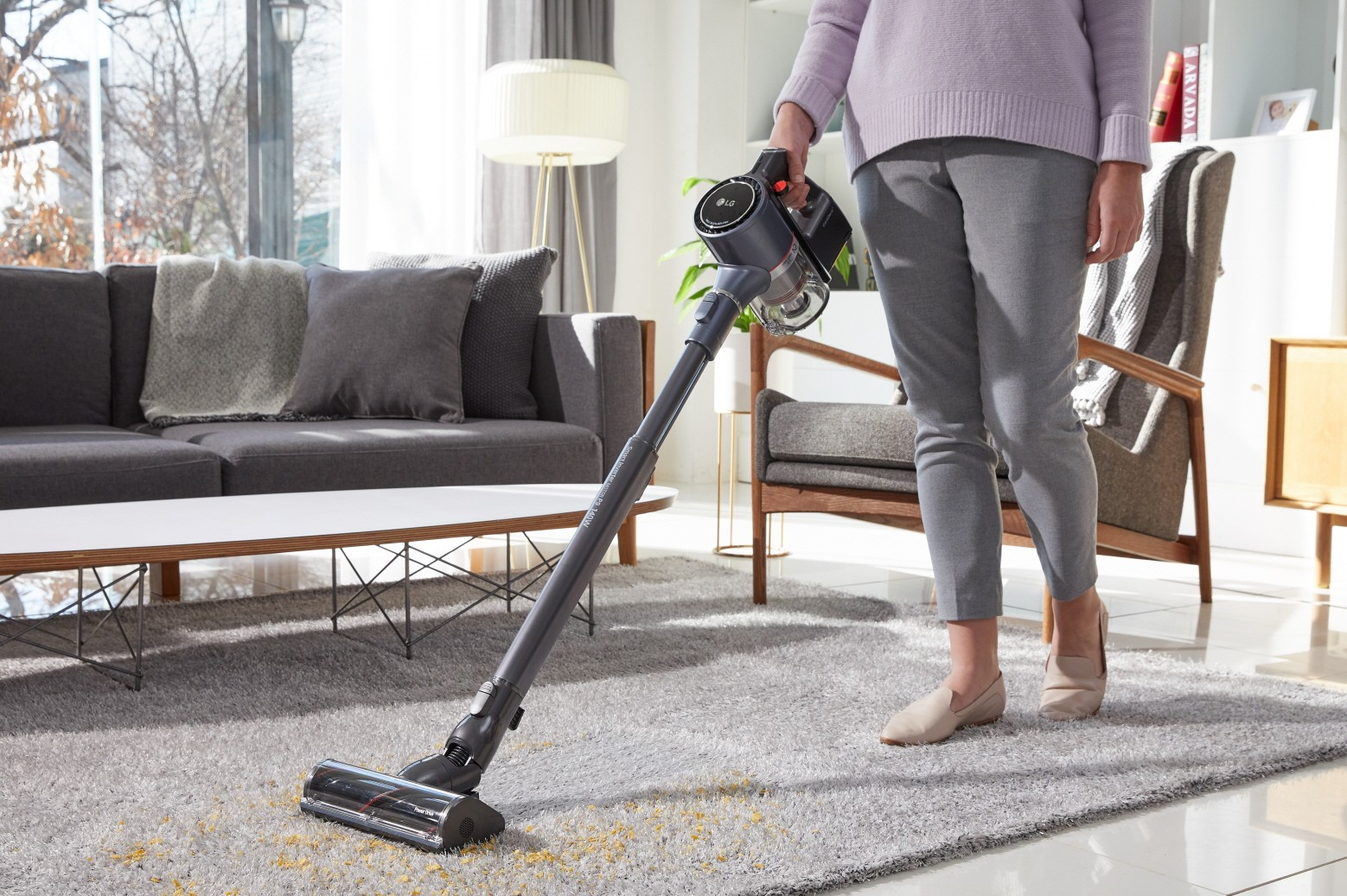 A woman vacuuming her living room carpet with LG CordZeroThinQ A9 Stick Vacuum, which is absorbing dust from the carpet.