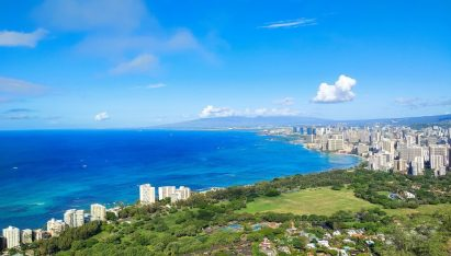 A wide-angle landscape photo taken by LG G8X ThinQ captures the beautiful blue sea and green hills of a town by the beach in Honolulu, Hawaii on a sunny day.