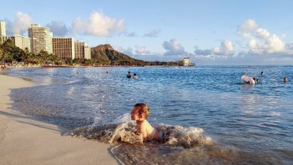 A photo taken by LG G8X ThinQ captures the special moment of a child splashing in the waves on the shore of a Hawaiian beach.