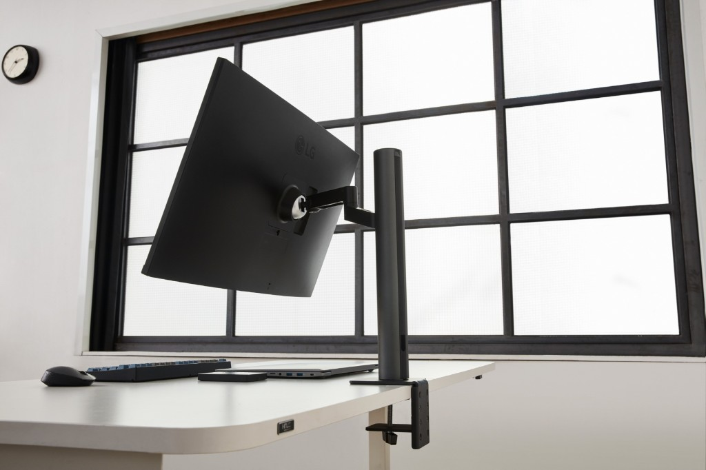 Rear side view of the LG UltraFine monitor 32UN880 with its clamp tightly holding the edge of the desk