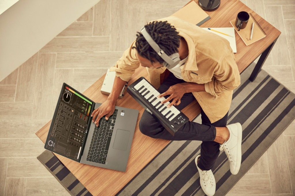 A man using his LG gram model 17Z90N with a piano keyboard to work on his music while sat on a bench, all without the need for a charger