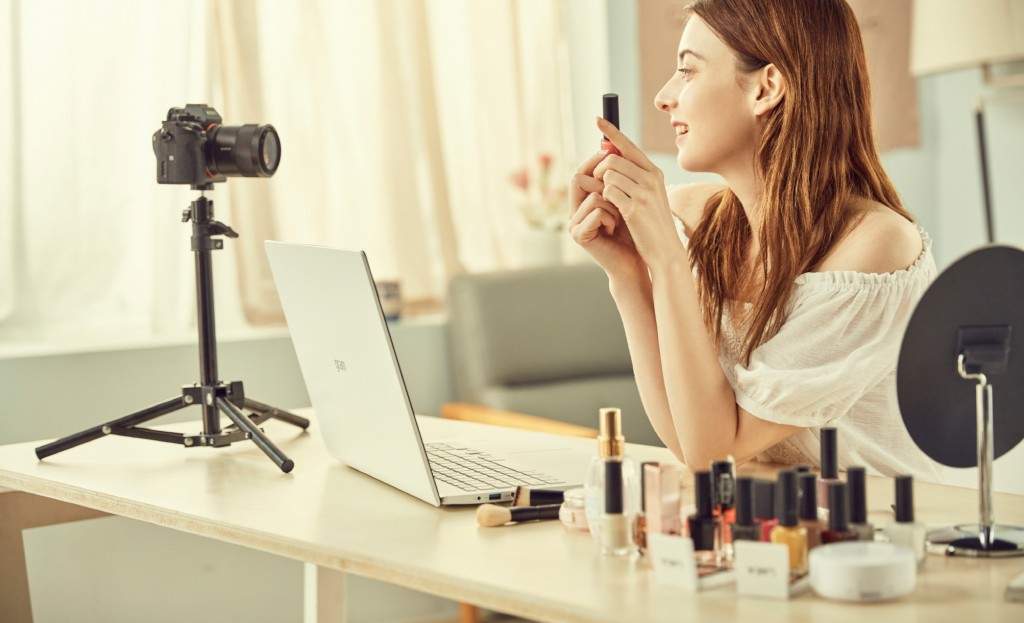 A female video creator demonstrating how to apply makeup via a camera and her LG gram model 17Z90N on the desk in front.