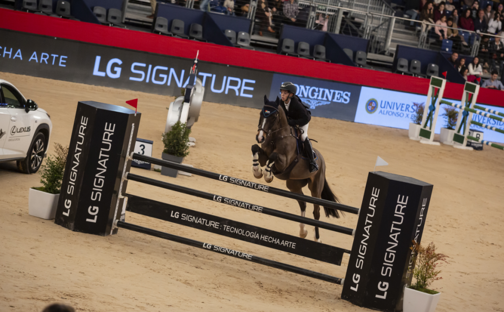 A rider and her horse leap over a tall hurdle at an equestrian competition while the jump displays the LG SIGNATURE logo to highlight the brand as the main sponsor.