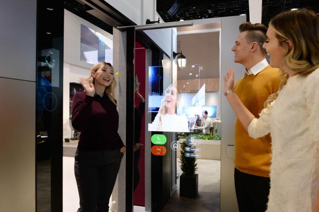 A woman waves to her friends after using LG ThinQ's Smart Door concept which was showcased at CES 2020