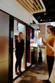 Another view of a woman waving to her friends after using LG ThinQ's Smart Door concept which was showcased at CES 2020