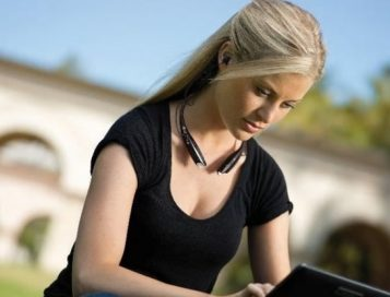A woman wears the world's first LG Tone Ultra HBS-800 behind-the-neck Bluetooth stereo headset while working on her laptop outdoors.