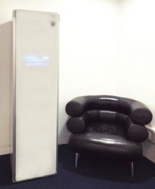The LG Styler is positioned next to a luxury leather-upholstered chair at the UK launch event