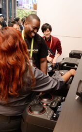 Some CES attendees try out the turntables and crossfaders on LG's XBOOM Speaker.