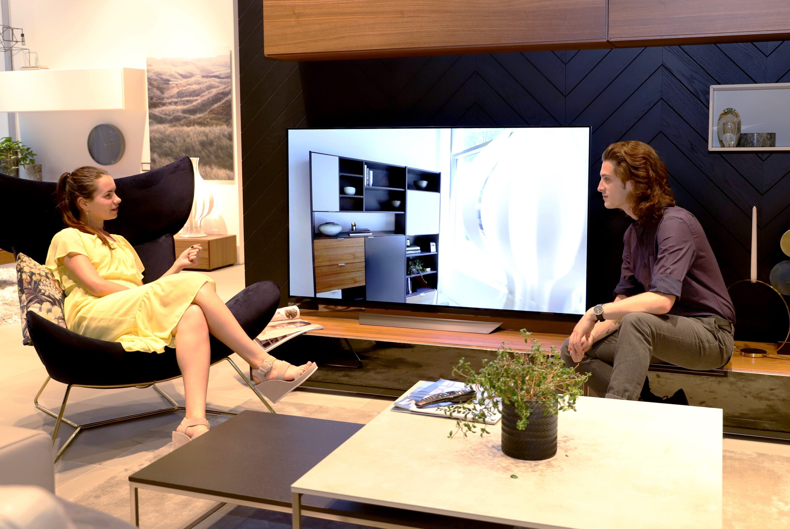 A man and a woman sit in the sample AI-enabled living room discussing LG's AI ThinQ-enabled TVs
