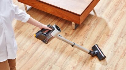 A woman uses the LG CordZero A9 vacuum cleaner to clean the wooden floor