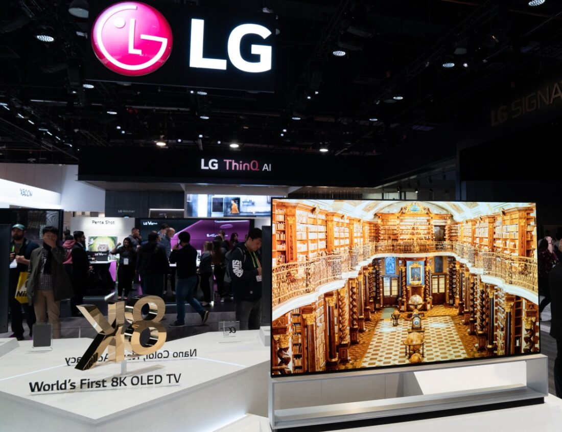 Front view of an LG 8K OLED TV set positioned on the right side of a promotional sign saying