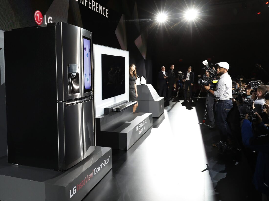 Side view of a female model posing next to LG SIGNATURE OLED TV W and LG CLOi Robots on stage while reporters take pictures at LG's CES 2017 Press Conference.