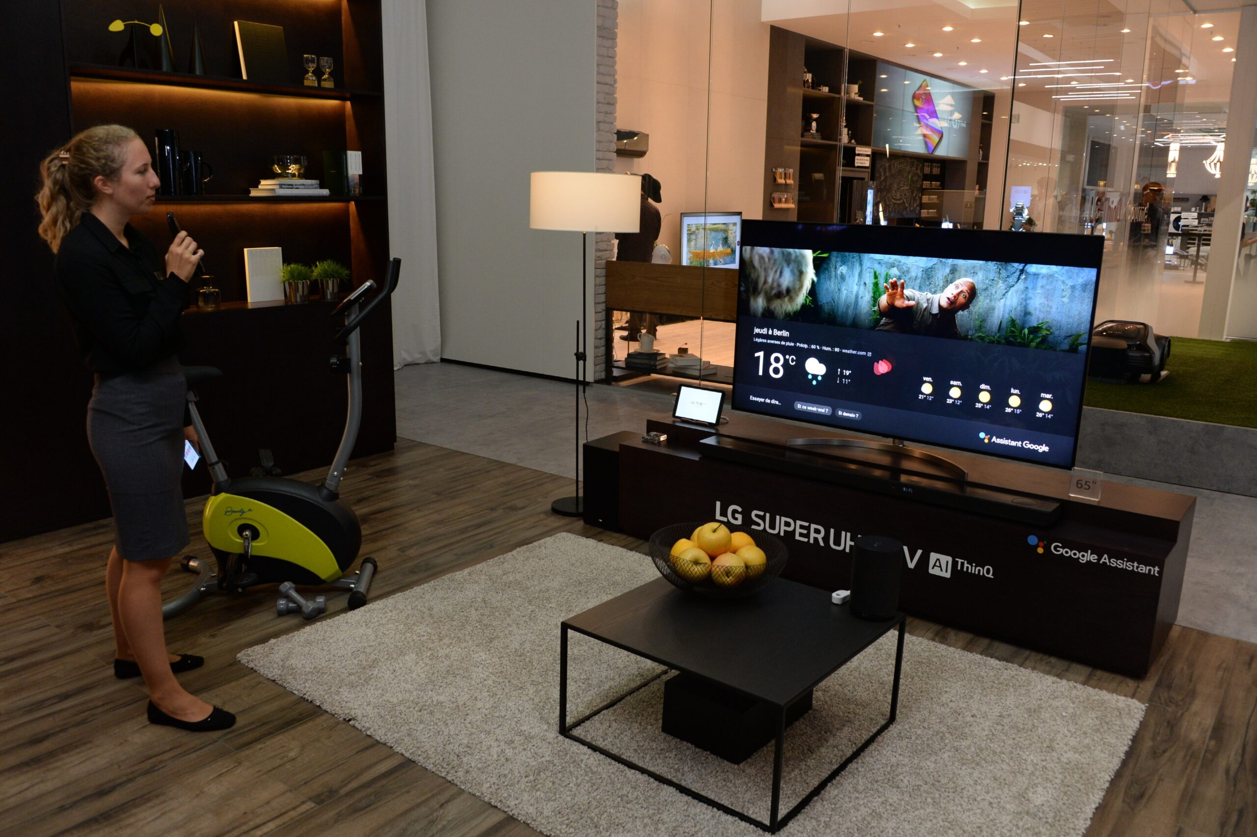 A female attendant holding the Magic Remote stands next to the LG SUPER UHD TV AI ThinQ with Google Assistant to try out the AI voice assistant feature.