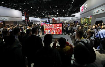 A drove of attendees and reporters at CES 2017 look at the screen of the LG SIGNATURE OLED TV W at LG's booth.