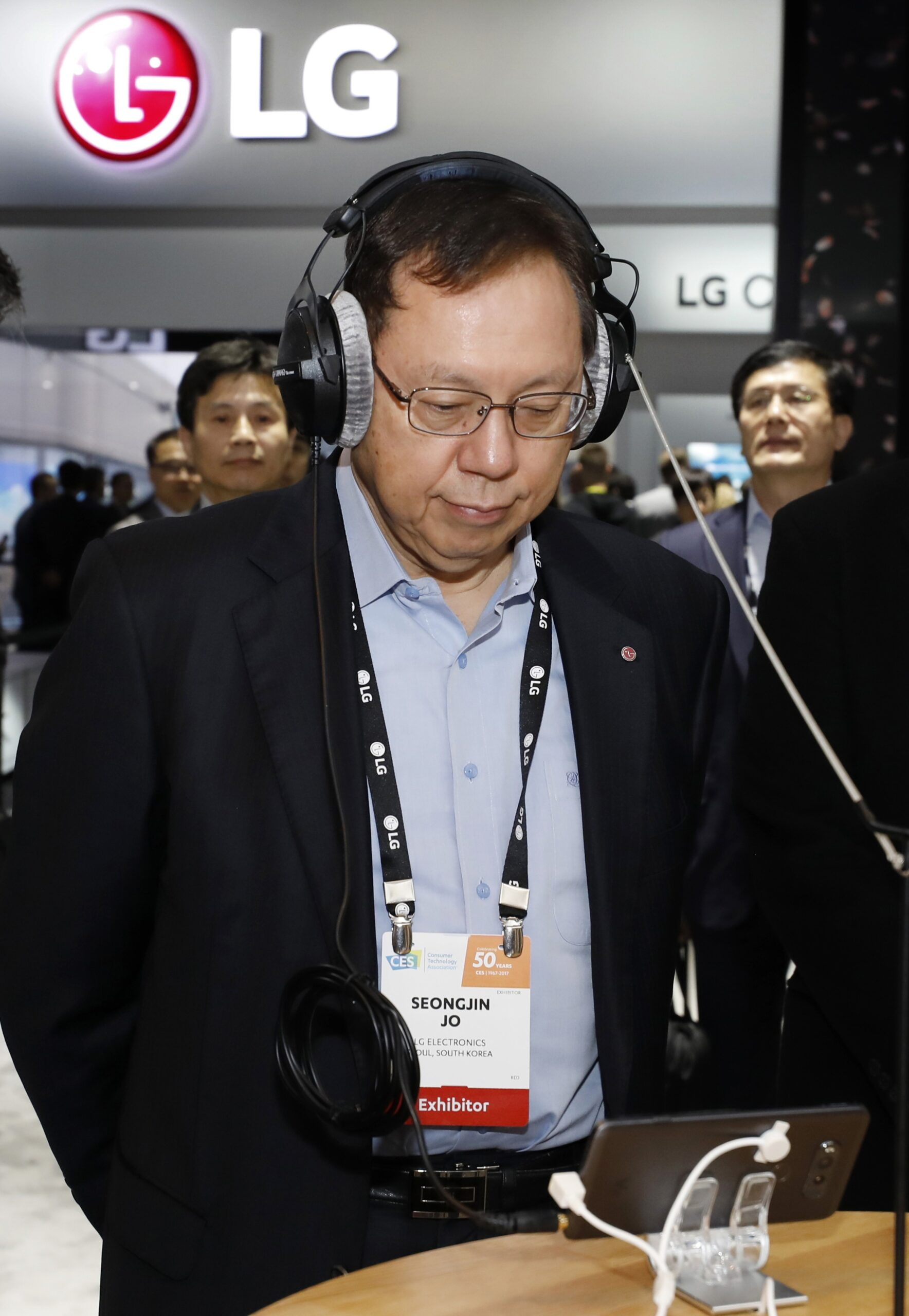 Jo Seong-jin, Vice Chairman and Chief Executive of LG Electronics tests the sound quality of LG's new smartphone via headphones at the company's CES booth.