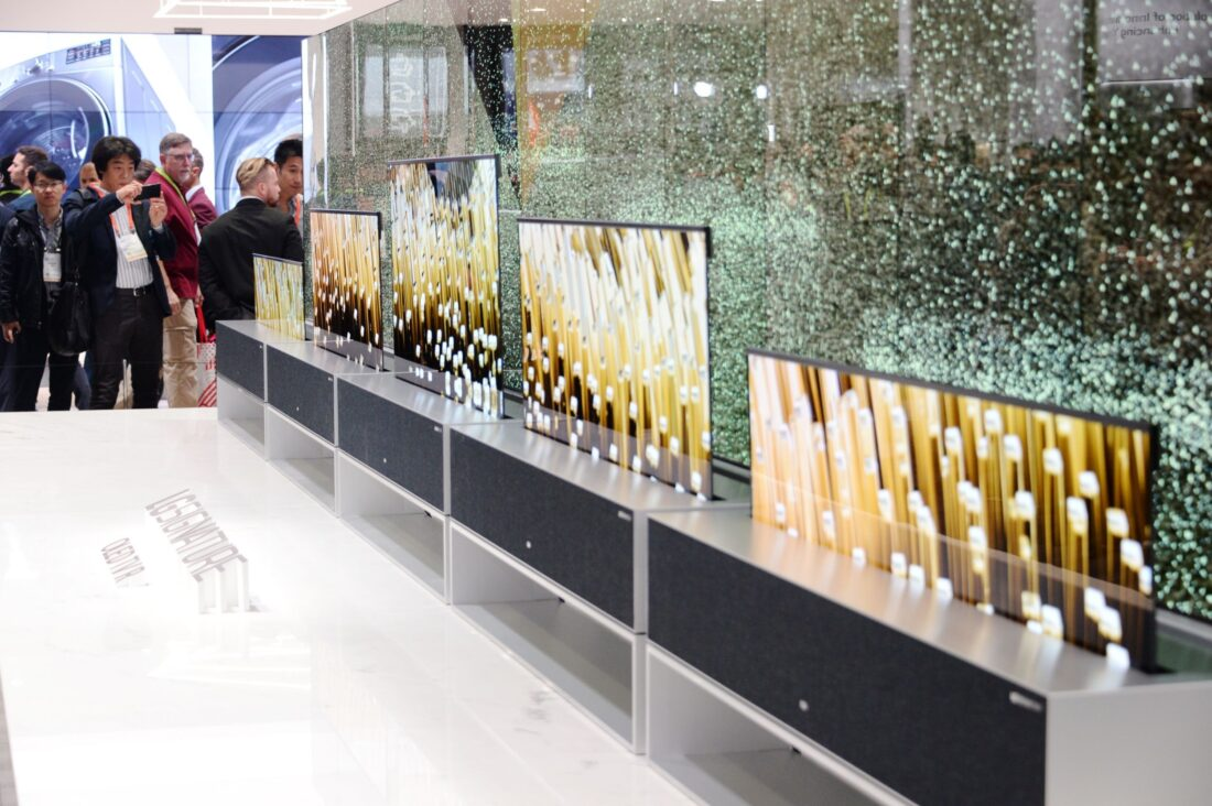 Closer view of LG SIGNATURE OLED TV R display zone with CES visitors viewing the display and taking pictures