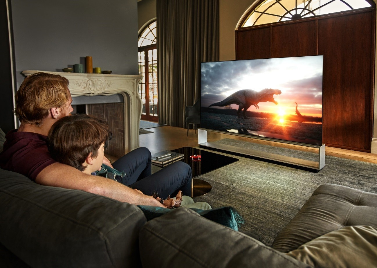 Father and son sit together in their living room to watch dinosaurs come to life on their LG TV