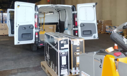 LG OLED TVs being loaded into the back of a van