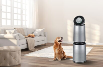 LG PuriCare Air Purifier Pet standing by a dog with a long, fluffy hair in a living room