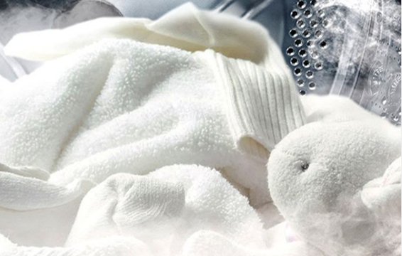 A close-up of soft white clothes being cleaned inside one of LG's washing machines
