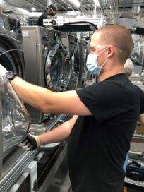 Another factory worker checking the quality of an LG washing machine's door