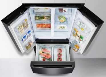A high view of the LG kimchi refrigerator with all its doors opened and each of its expansive sections filled with diverse foods and drinks
