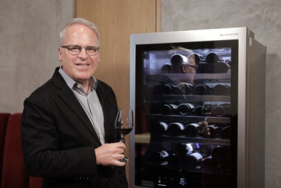 Wine critic and global brand ambassador James Suckling poses next to LG SIGNATURE wine cellar with a glass