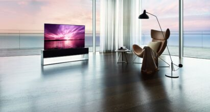 LG SIGNATURE OLED R placed inside a bright modern space with expansive windows in Full View mode, its true-to-life color displaying a perfect sunset that harmonizes with the equally beautiful coastal view outside