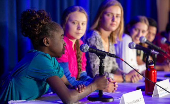 A 12-year-old girl discussing environmental issues with other inspiring young individuals, including Greta Thunberg, during a United Nations Committee event