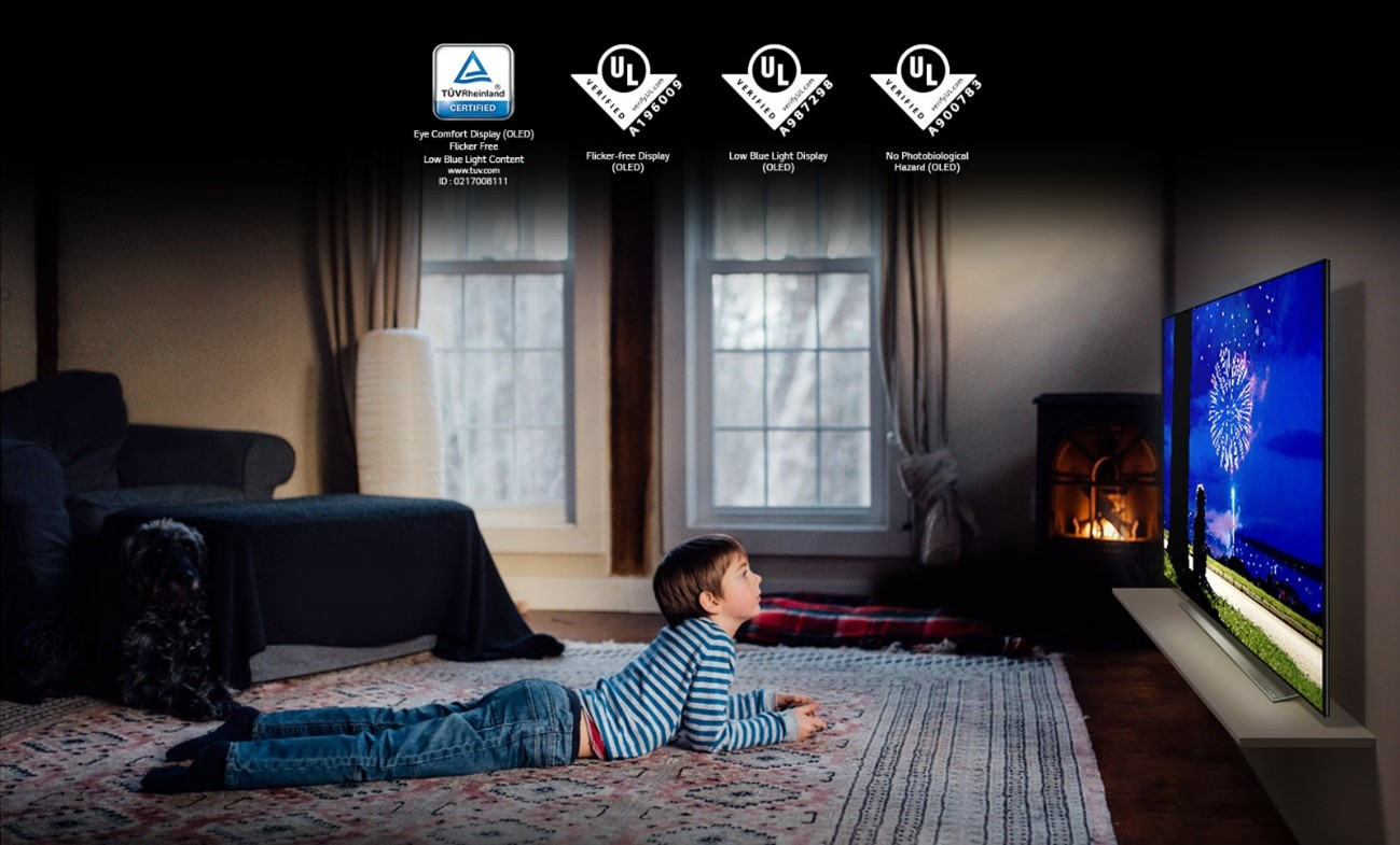 A boy lying on his cozy living room while watching a firework display on the LG OLED TV that gives off less blue light