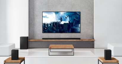 The LG Soundbar sitting on a wooden shelf below a wall-mounted LG TV complements the TV's sound while perfectly blending into the modern room's interior