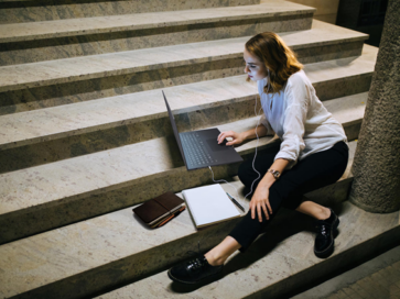 A woman casually sitting down on the stairs while working with her LG gram and a notebook.