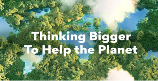 """An Aerial Photo of a forest with lakes representing the world's continents and the phrase """"Thinking Bigger To Help the Planet"""" overlapping."""
