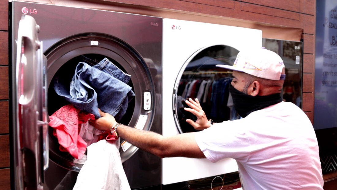 A man putting laundry into the LG washing machine so that they are fully sanitized and hygienic before being donated to local beneficiaries