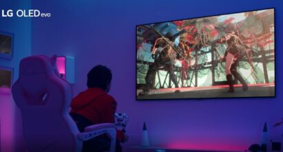 A gamer playing on LG OLED TV in a room boasting atmospheric purple and blue lighting