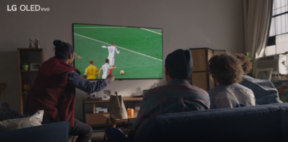 Four friends enjoying a game of football on LG OLED TV