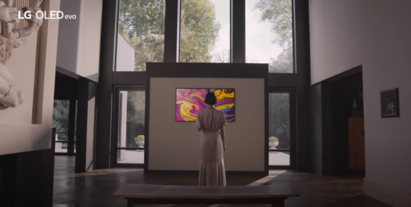 A woman admiring a vivid painting being displayed on an art gallery's LG OLED TV