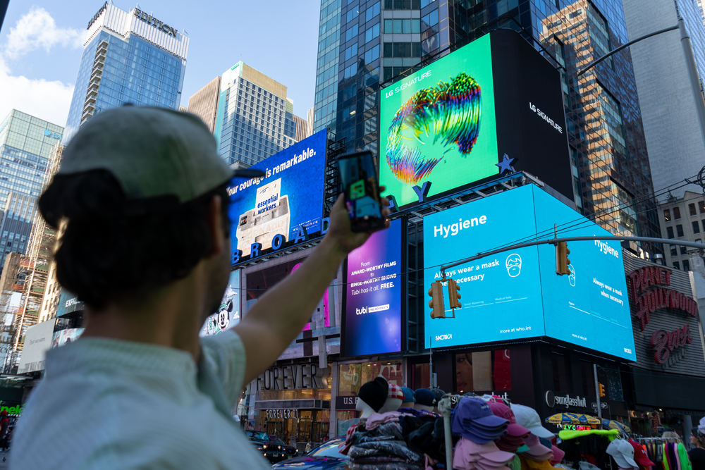 A man taking a picture of LG's massive, high-definition digital billboard in Time Square, New York displaying the artwork of David McLeod