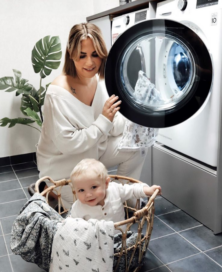 A woman using an LG washing machine to do her laundry as her baby plays inside the clothes basket.