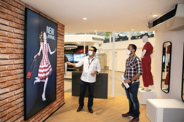Two men admiring LG signage as it displays a fashion model in a white and red patterned dress.