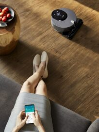 A woman sitting on a sofa as she uses the LG ThinQ app on her smartphone to control the robot vacuum cleaner