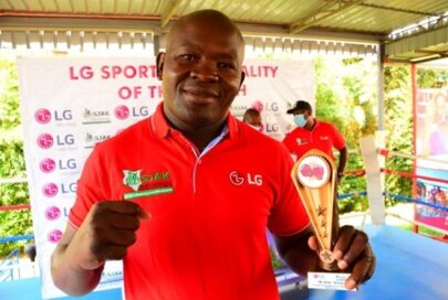 A photo of boxer Elly Ajowi making a proud fighting pose while holding his LG trophy