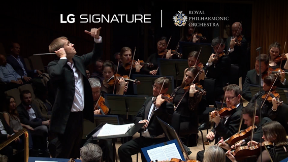The conductor and violinists of the Royal Philharmonic Orchestra during a performance with the logos of LG SIGNATURE and the orchestra above