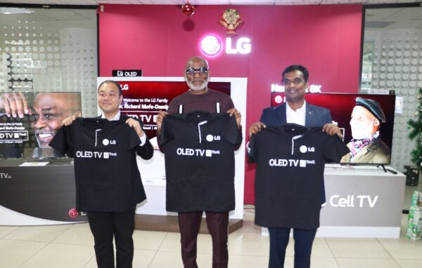 Nigeria's Richard Mofe-Damijo holds up an LG OLED TV shirt with two LG representatives.