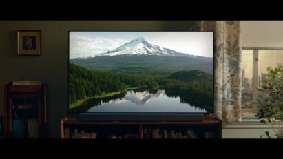 LG's TV displays a beautiful mountain, forest and lake inside a living room.