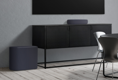 The black LG Éclair and subwoofer placed below a wall-mounted LG TV to effortlessly blend into a grey contemporary living space